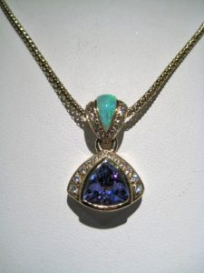14K Gold Pendant with Opal, 1.64c Tanzanite, and .31c Diamond Artist: Kabana Stavros Catalog: 895-94-9 #18937 Price: $7,500.00 REDUCED: $3,900.00 CHAIN SOLD SEPARATE PRICE: $550.00 REDUCED: $275.00